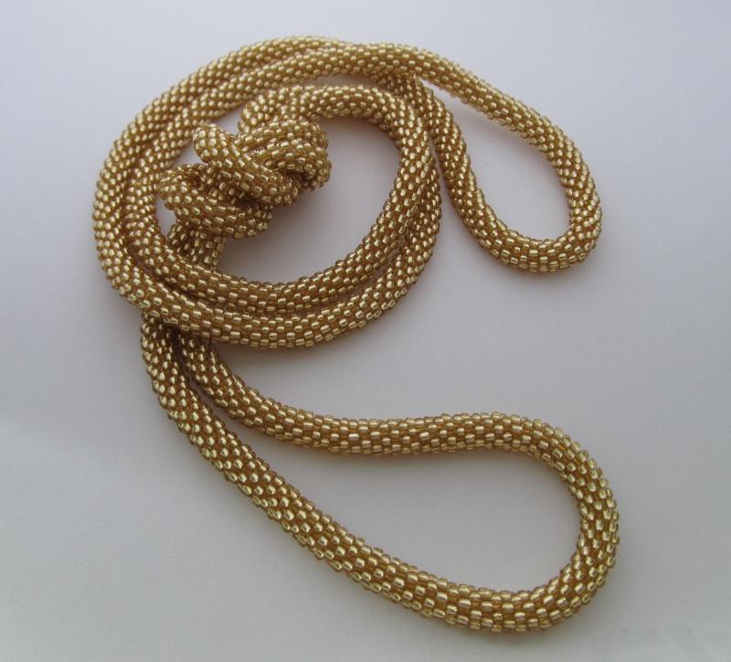Жгут бисерный, золотистого цвета, длиной 110 см.